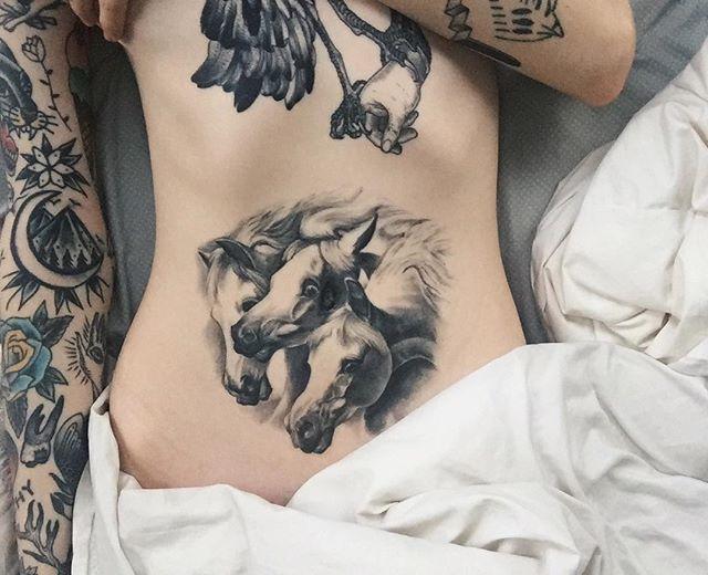 Vemos la barriga de una mujer con tatuaje de caballos