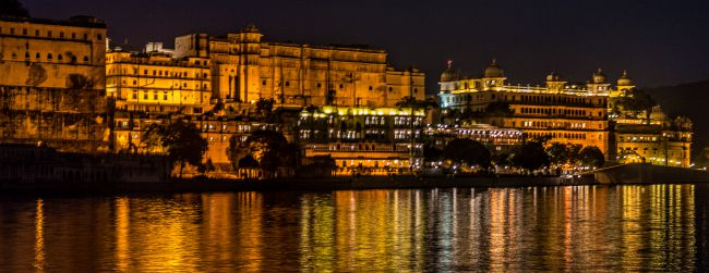 A lit up city Palace Udaipur in the evening with its reflections in Lake Pichola