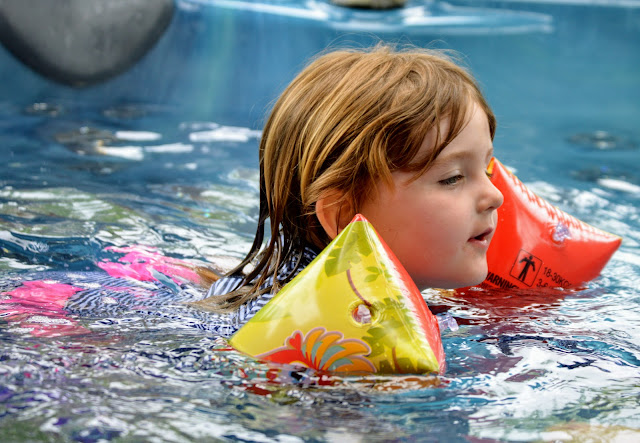 Image of little girl swimming in toucan arm bands across a hot tub.