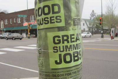 Lime green poster taped to a light pole, reading GREAT JOBS GOOD CAUSES