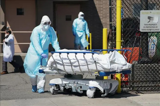 Medical staff move patients who died from COVID-19 to a hospital morgue in New York, USA. Photo: AFP