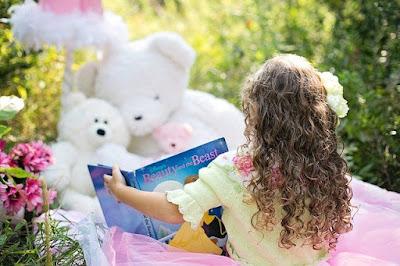 anak membacakan buku pada boneka