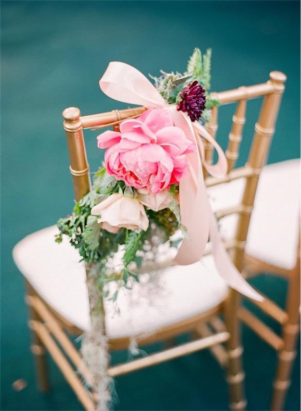 detalle floral en silla dorada boda decorada en fucsia y esmeralda chicanddeco