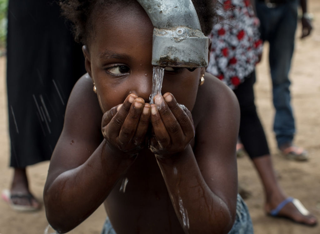 A child drinks some water at a newly sunk borehole, dug using a manual drill at a village in the west districts of Kinshasa so that women and childrens do not have to walk long distances to reach small and often polluted river on march 7, 2015. Drilling of wells by hand is a common technique in rural D.R. Congo, a technique 4-5 time cheaper than the classic one and can be operated in remote areas where it would be near impossible to bring the materials for mechanical drilling. AFP PHOTO/FEDERICO SCOPPA / AFP PHOTO / FEDERICO SCOPPA (Photo credit should read FEDERICO SCOPPA/AFP via Getty Images)