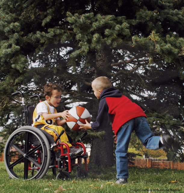 Two boys playing in a yard, with a  red and white basketball. One is in a wheelchair, handing the ball to the other, who is running to grab it
