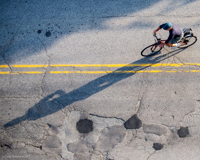 Portland, Maine USA June 2017 photo by Corey Templeton. A cyclist and their shadow heading down Pearl Street in the Old Port.