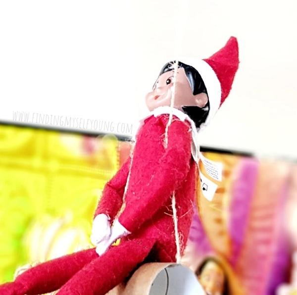 elf on the shelf swinging on a swing