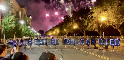 "Protestors with signs saying ""Trump failed 180,000+ died"" while fireworks go off behind them with Washington Monument in background"