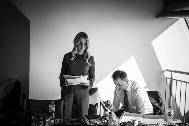 Władysław Kosiniak-Kamysz przegląda smartfona a jego żona stoi i spogląda na kartki papieru trzymane w ręku