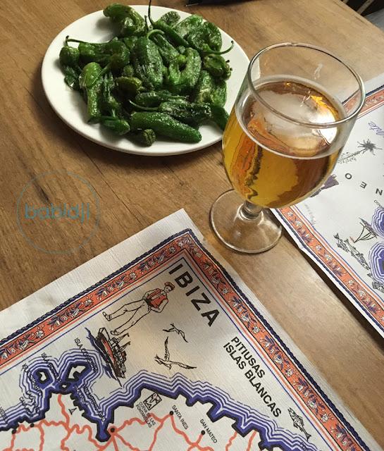 assiette de tapas de pimientos de padron et une bière pression sur une table de restaurant Porto Salc à Ibiza