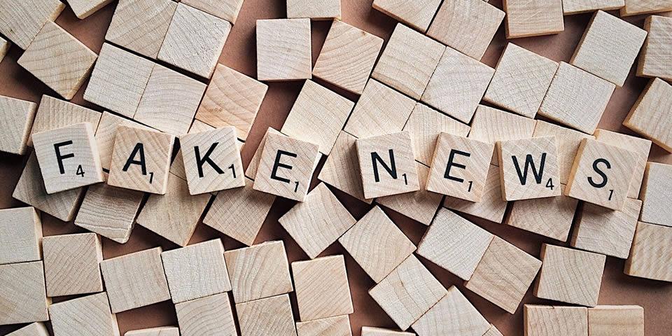 Blocos de madeira com letras da palavra fake news