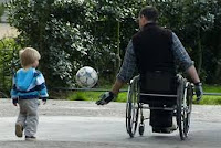 Male wheelchair rider with boy tossing a soccer ball