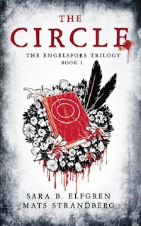 A red book dripping with blood atop a garland with flowers and two black feathers.