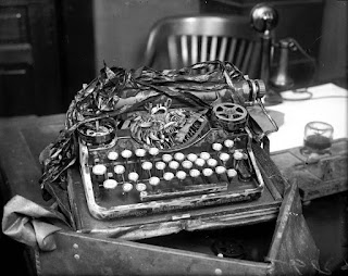Black and white image of an Underwood typewriter circa 1920s. The keyboard, reels and ribbon are all damaged, some keys are missing. The typewriter sits on a desk with an old-fashioned chair in the background and a telephone of the old two-piece (ear and mouth pieces) type.