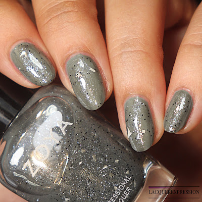 Swatch of a nail polish glitter topper by Zoya called Theo over a sage green polish