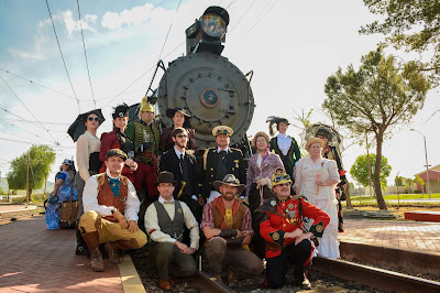 Steampunk cosplayers pose in front of iron horse steam train