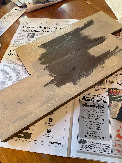 Photo of dark stained boards being painted in Putty