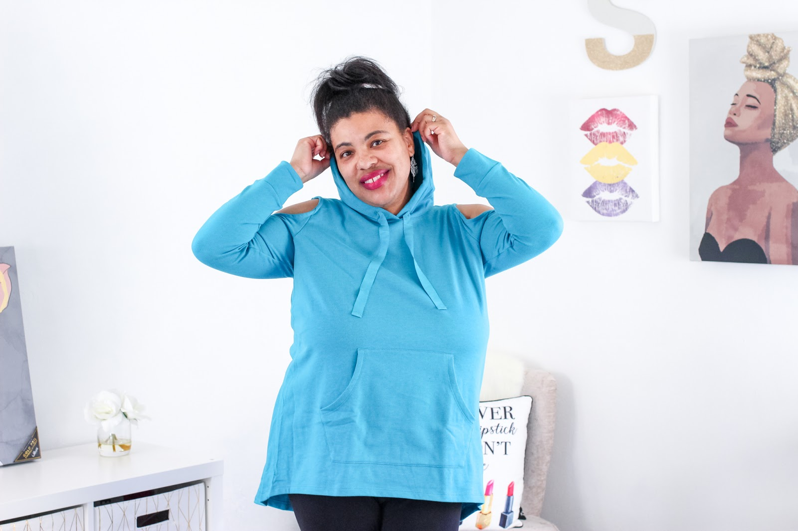 a black woman wearing a turquoise hoodie