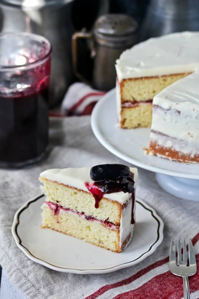 This cardamom cake is frosted with a sweet mascarpone icing and filled with a boozy mulled wine jam with black grapes and plums.
