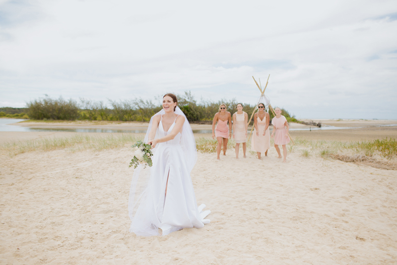 bride throwing bouquet on beach