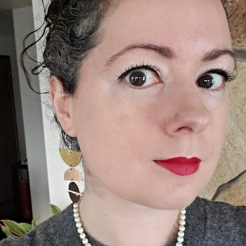 Woman wearing geometric dangling metallic leather and sterling silver earrings and pearls.