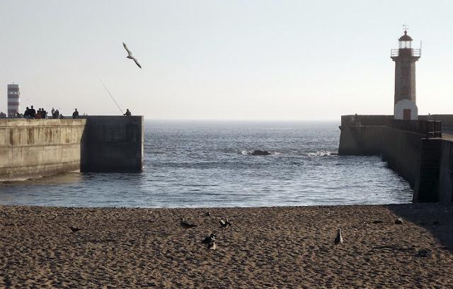 Faróis, praia, areia e pessoas num paredão