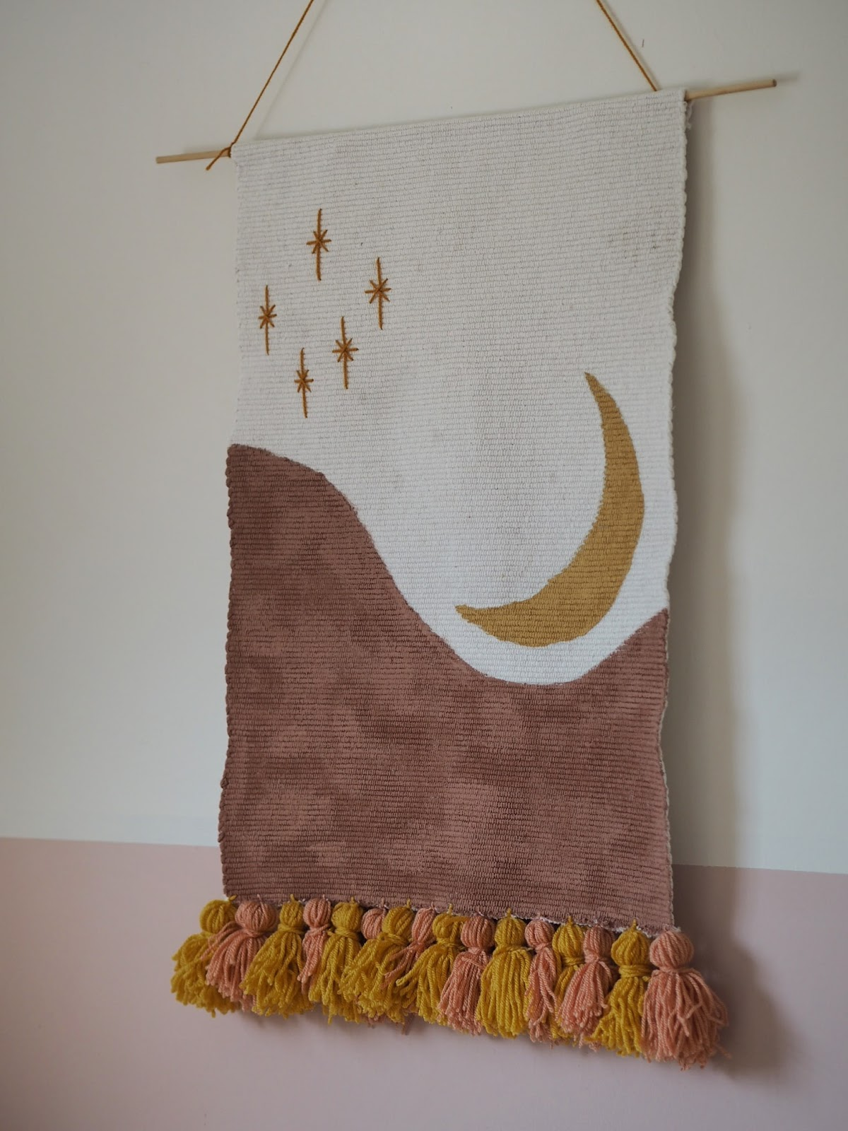 How to make a DIY wall hanging from an old bath mat. In a boho style, and featuring woollen tassels and a hand-painted moon and stars pattern, this feature is the perfect accessory to any blank wall. Simple, low budget DIY tutorial craft project.