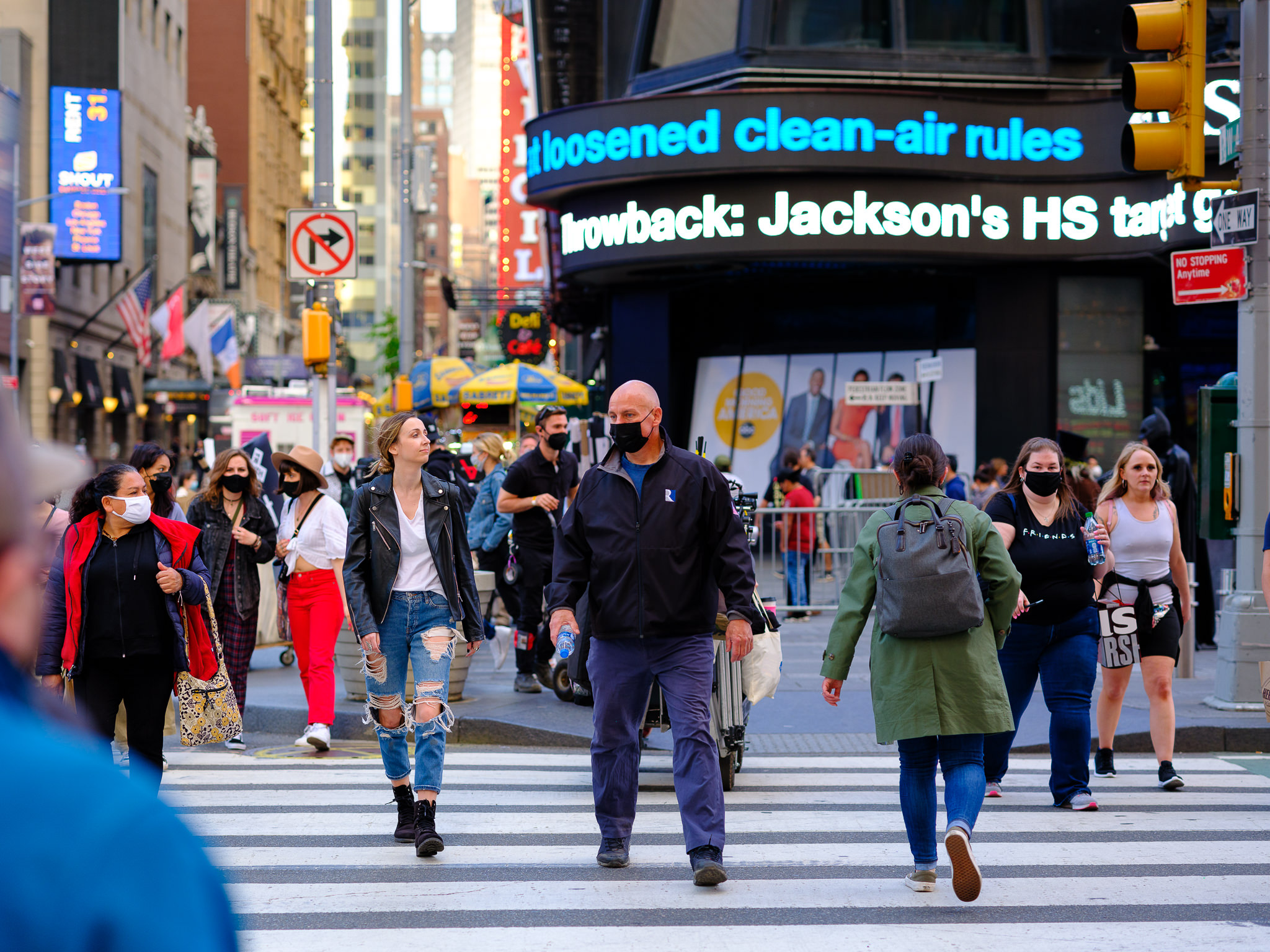 a photo of people in a crosswalk in times square new york city