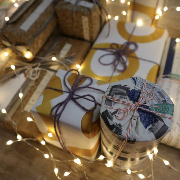 beautifully wrapped gifts surrounded by white lights and greenery