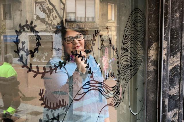 La ilustradora Sandra Erre decora un escaparate de la calle Portu