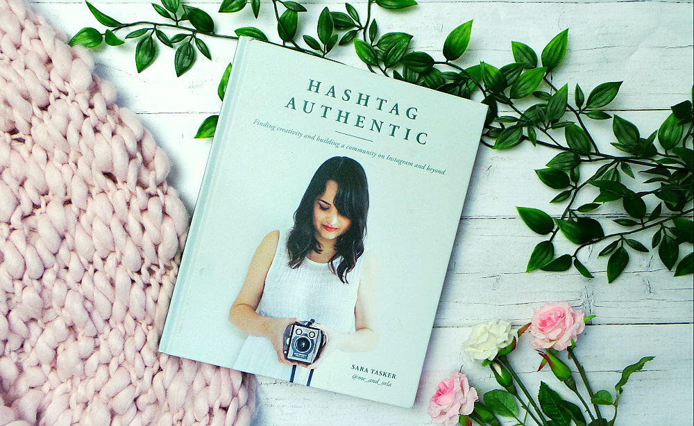 The hashtag authentic book next to a pink chunky knit blanket and some roses. The cover shows Sara wearing white looking down at a camera in her hands