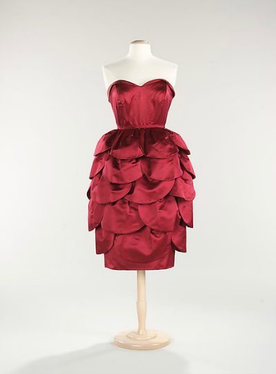 Cranberry colored tulip skirt cocktail dress designed by Mainbocher in 1955 displayed on dress stand