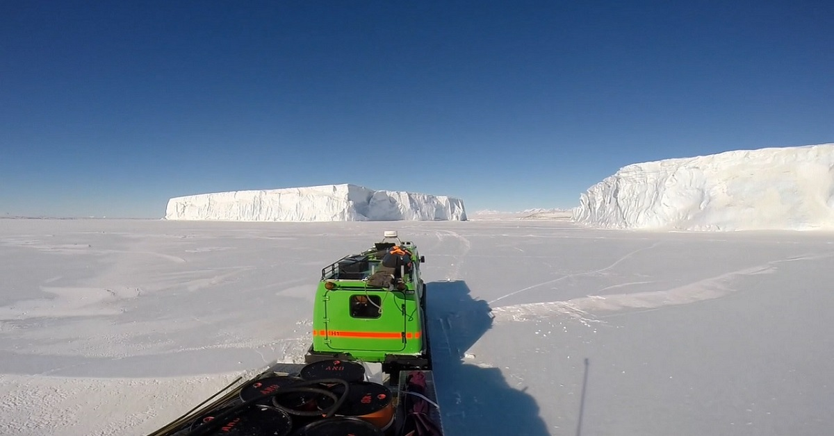 driving across the sea ice between huge icebergs in antarctica
