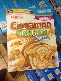 A box of Millville Cinnamon Crunch Squares cereal, sitting atop other cereal boxes