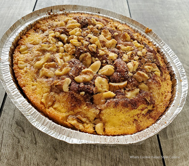 this is a sour cream doctored cake me cake in a round disposable pan with cinnamon  sugar and nuts on top