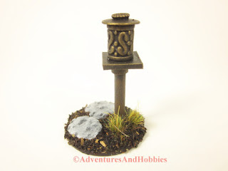 Miniature metal shrine T1562 on wooden pole - side view.