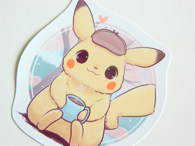 A photo featuring a sticker by artist Naomi Lord, Detective Pikachu holding a mug of coffee
