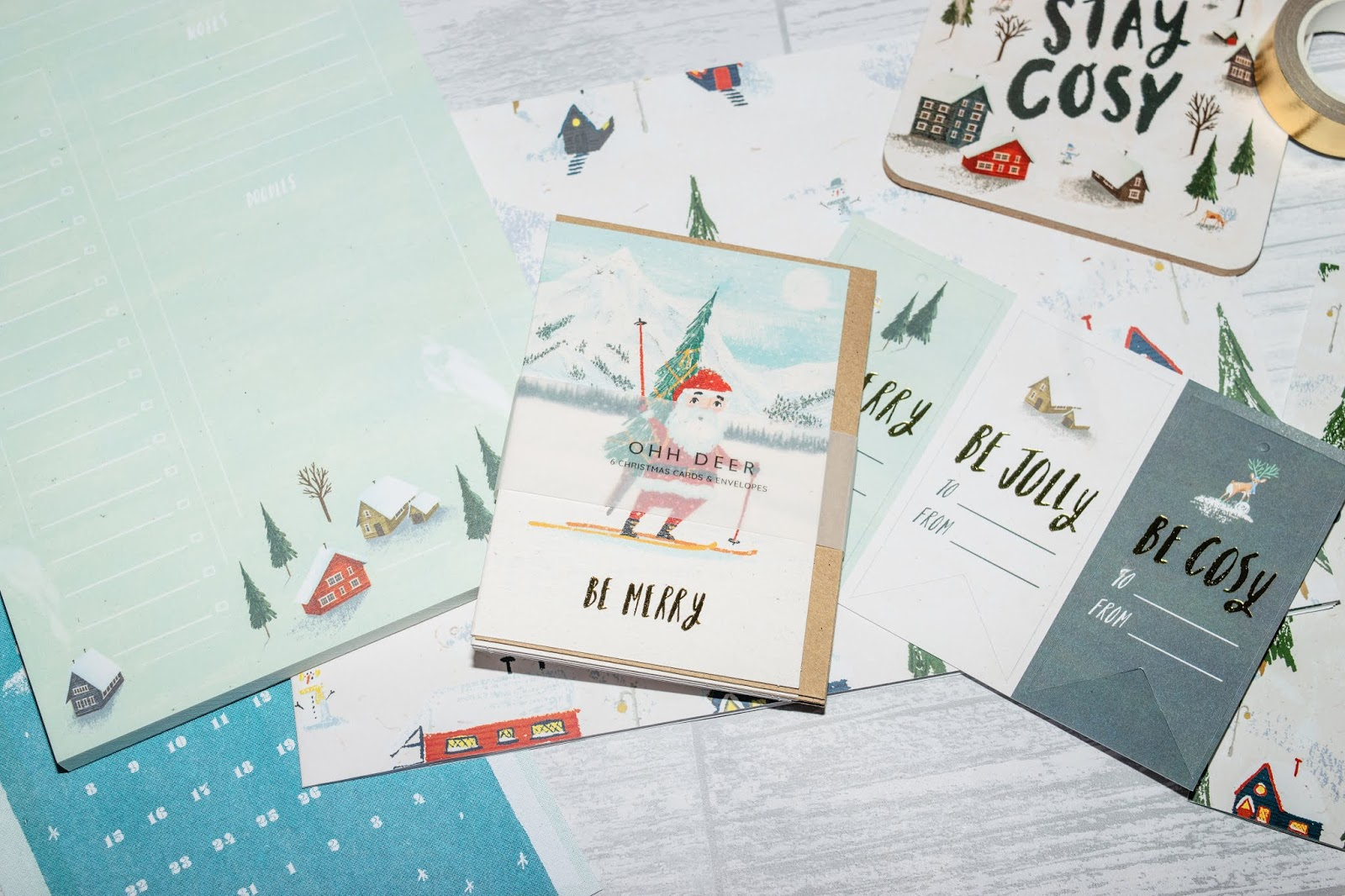 A pack of winter forest themed Christmas cards. The front design is Santa Claus on skis.
