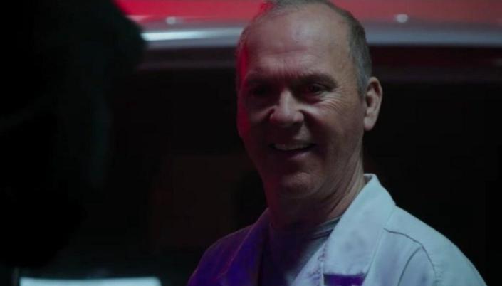 Imagem: o personagem Abutre, interpretado por Michael Keaton, sorrindo, em um jaleco branco, com uma luz avermelhada por trás.