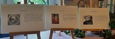 Zdjęcie przedstawia trzy sztalugi. Na pierwszej znajduje się zdjęcie Eratostenesa wraz z krótką biografią . Na drugiej sztaludze znajduje się zdjęcie Laury Bush oraz jej krótka biografia. Na trzeciej sztaludze znajduje się zdjęcie Adama Mickiewicza wraz z krótką biografią.