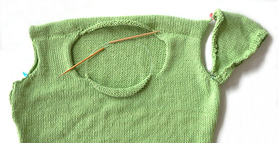 Knitting in progress of green Cable Collar Top with shifted shoulder seams on a white background