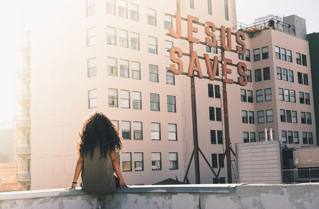 curly hair woman sitting on the edge of roof top looking at Jesus Saves sign