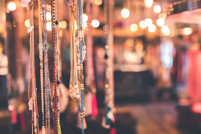Beaded necklaces hung for display at a bazaar.