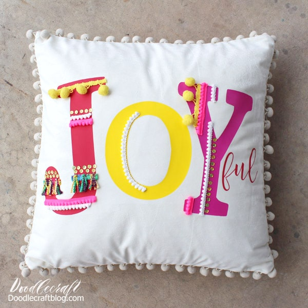 Make a joyful pom-pom pillow inspired by Anthropologie in this fun and simple tutorial. Using brightly colored iron-on vinyl and colorful trims and pom-poms to make the Joy pop!