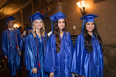 photo of 4 students in blue gowns and caps smiling while walking to graduation