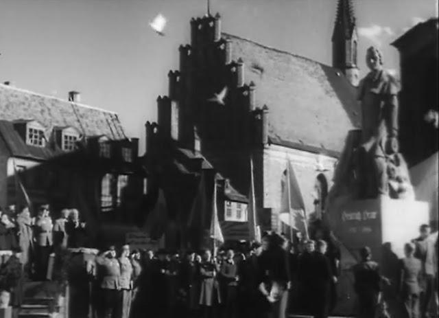 """Кадр из фильма """"Встреча на Эльбе"""". Сцена: торжественное открытие восстановленного памятника Генриху Гейне (1:32:50). Место съёмок: Рига, около собора Св.Петра."""