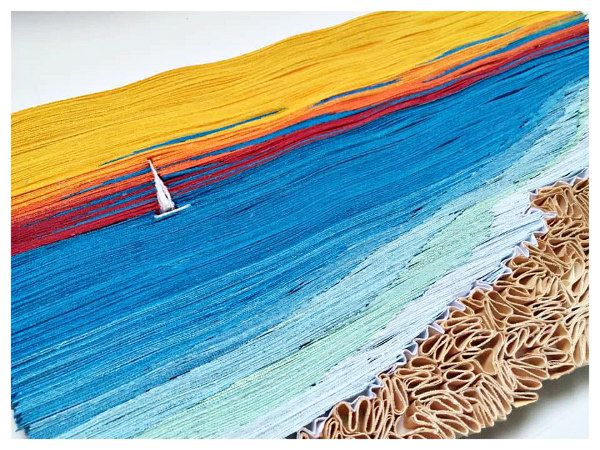 layered paper seascape with sailboat and beach made of paper strips and pinched paper shapes
