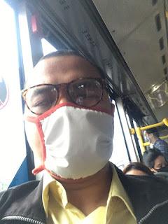 Foto Dimas Muharam dengan masker di bus Trans Jakarta