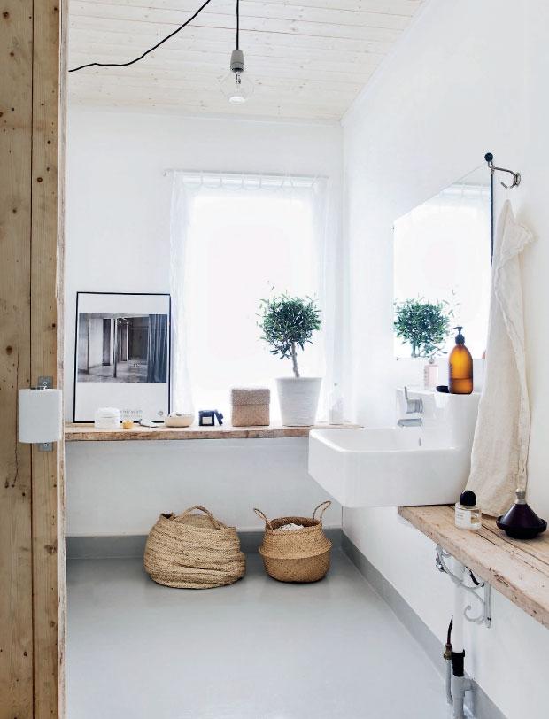 Cuarto de baño blanco con madera y cestas de mimbre