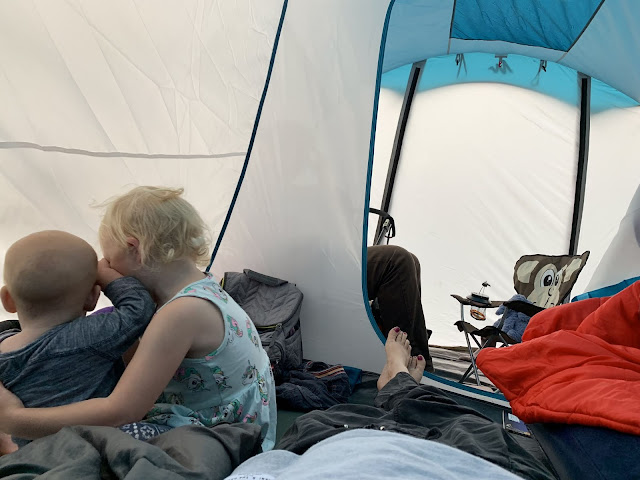 2 children cuddling in a tent with the zip to the sleeping pod open and looking to the communal area